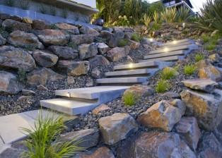 Haus in Neuseeland zu verkaufen. Eine Steintreppe führt von der Straßenebene zu Terrasse und Wohnbereich hoch.