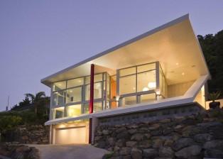 Blick von der Straße auf das hell erleuchtete Designerhaus über dem Meer.