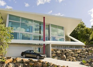 The front view shows how the house was spectacularly integrated into the hill above the sea. New Zealand.