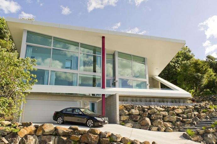 (deutsch) Die Frontansicht zeigt, wie das Haus spektakulär in den Berg überm Meer integriert wurde. Neuseeland.
