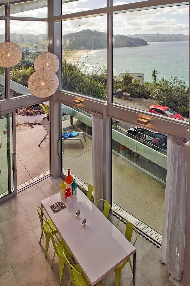 High ceilings and panoramic windows offer unobstructed views of the sea. NZ home purchase.